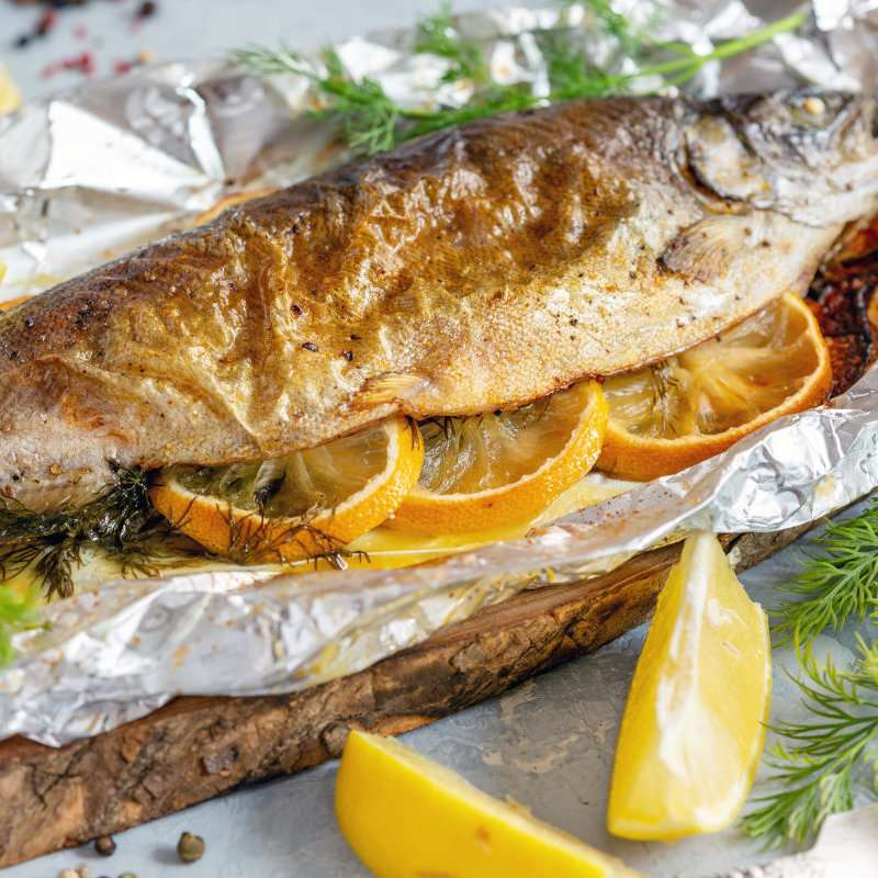 Trout with lemon slices and fresh dill baked in foil on a wooden serving board, selective focus.